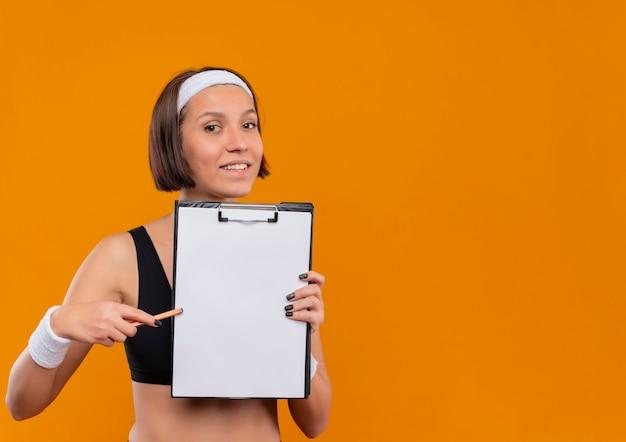 Mulher jovem fitness em roupas esportivas com tiara mostrando a prancheta com páginas em branco apontando com uma caneta para ela sorrindo amigável em pé sobre a parede laranja