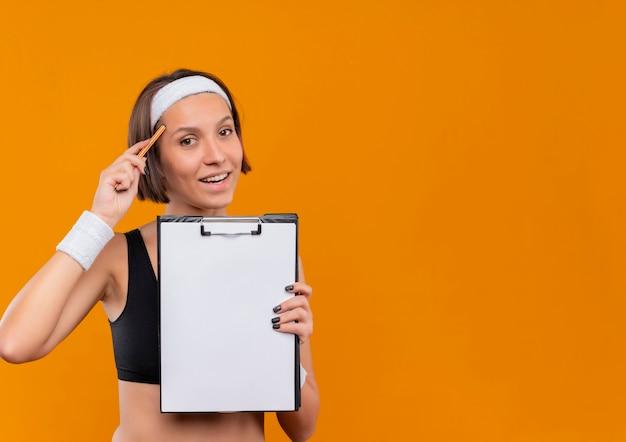 Mulher jovem fitness em roupas esportivas com tiara mostrando a prancheta com páginas em branco apontando com uma caneta para sua têmpora, parecendo confiante em pé sobre a parede laranja