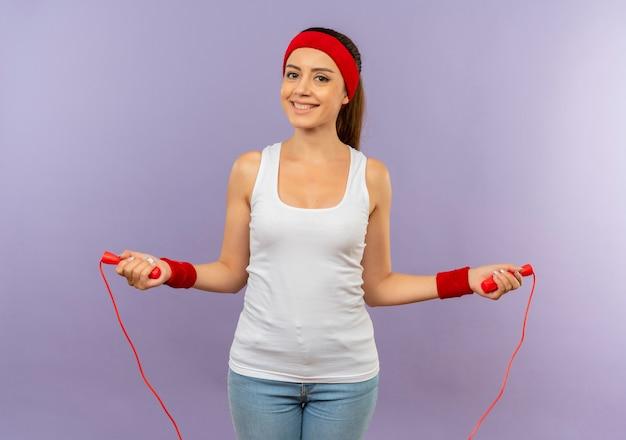 Mulher jovem fitness em roupas esportivas com tiara segurando corda e sorrindo alegremente indo pular de pé sobre a parede cinza