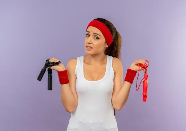 Mulher jovem fitness em roupas esportivas com tiara segurando cordas de pular, parecendo confusa, sem resposta em pé sobre uma parede cinza
