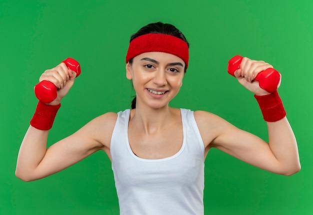 Mulher jovem fitness em roupas esportivas com tiara segurando dois halteres, levantando as mãos, fazendo exercícios, sorrindo confiante em pé sobre a parede verde