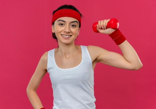 Mulher jovem fitness em roupas esportivas com tiara segurando halteres na mão levantada, sorrindo confiante em pé sobre a parede rosa