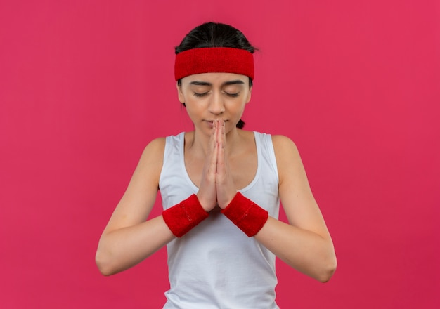Mulher jovem fitness em roupas esportivas com tiara segurando os braços juntos como orando com expressão de esperança com os olhos fechados em pé sobre a parede rosa