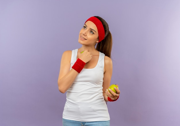 Mulher jovem fitness em roupas esportivas com tiara segurando uma maçã verde, olhando de lado feliz e positiva em pé sobre a parede cinza