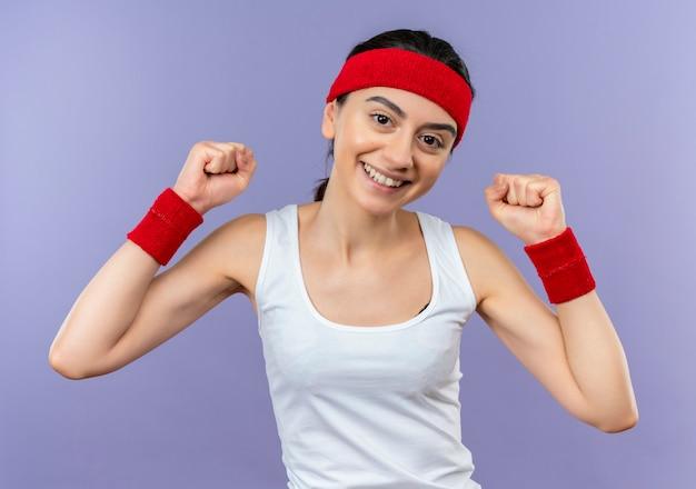 Mulher jovem fitness em roupas esportivas com tiara sorrindo alegremente cerrando os punhos, feliz e positiva em pé sobre a parede roxa