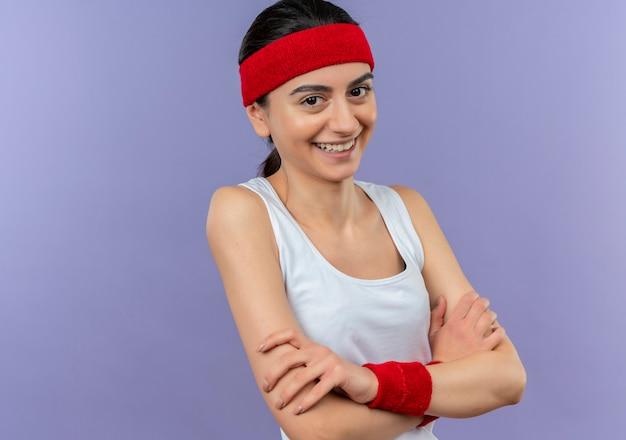 Mulher jovem fitness em roupas esportivas com tiara sorrindo alegremente com os braços cruzados no peito em pé sobre a parede roxa