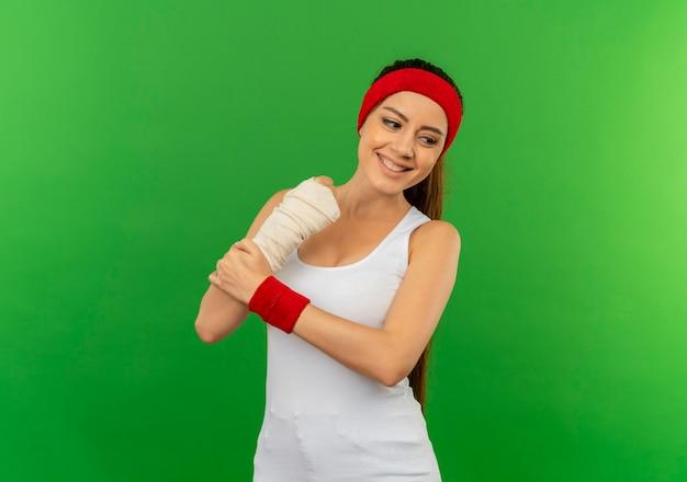 Mulher jovem fitness em roupas esportivas com tiara tocando seu braço enfaixado sorrindo positiva e feliz em pé sobre a parede verde