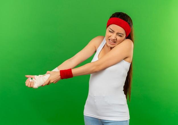 Mulher jovem fitness em roupas esportivas com uma faixa na cabeça tocando seu braço enfaixado, parecendo indisposta em pé sobre a parede verde
