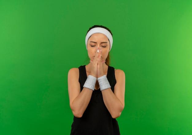 Mulher jovem fitness em roupas esportivas, de mãos dadas como orando com expressão de esperança em pé sobre a parede verde