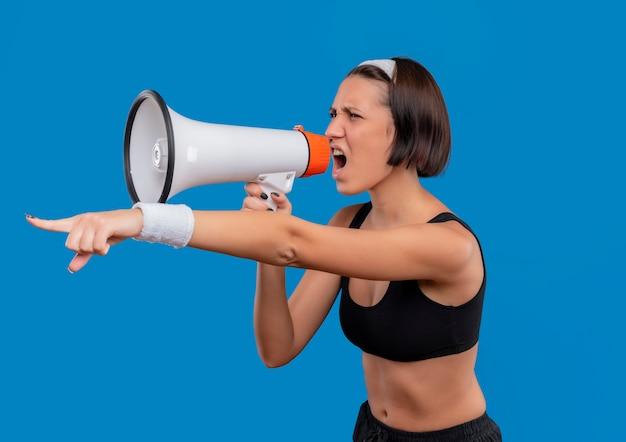 Mulher jovem fitness em roupas esportivas gritando para o megafone com uma expressão agressiva apontando com o dedo indicador para algo em pé sobre a parede azul