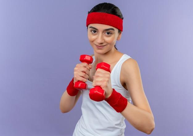 Mulher jovem fitness em roupas esportivas segurando dois halteres, posando como um boxeador em pé sobre a parede roxa