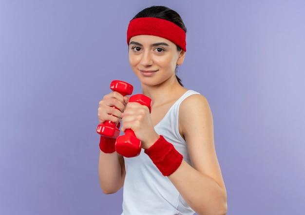 Mulher jovem fitness em roupas esportivas segurando dois halteres, posando como um boxeador, parecendo confiante em pé sobre a parede roxa
