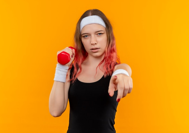 Mulher jovem fitness em roupas esportivas segurando halteres apontando com o dedo indicador para a câmera com uma cara séria em pé sobre a parede laranja