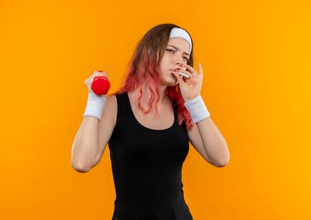 Mulher jovem fitness em roupas esportivas segurando halteres e fumando um cigarro em pé sobre uma parede laranja