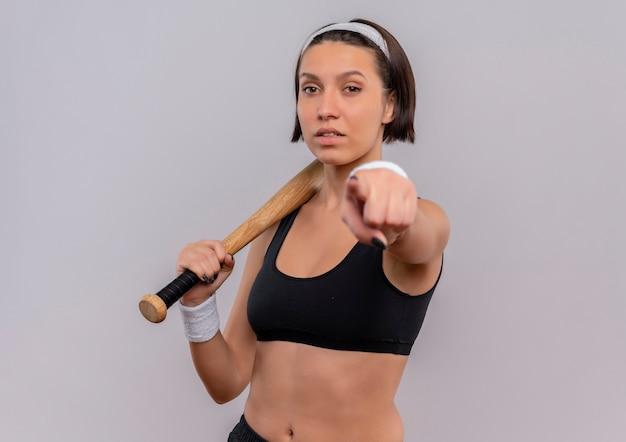 Mulher jovem fitness em roupas esportivas segurando taco de beisebol apontando com o dedo para você, parecendo confiante em pé sobre uma parede branca