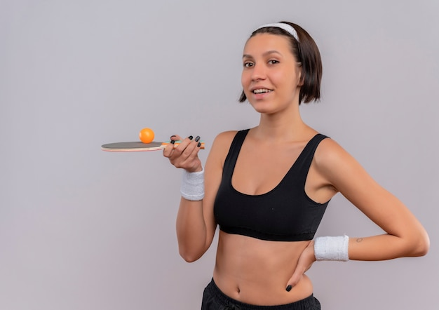 Mulher jovem fitness em roupas esportivas segurando uma raquete e uma bola de tênis de mesa, sorrindo alegremente em pé sobre uma parede branca
