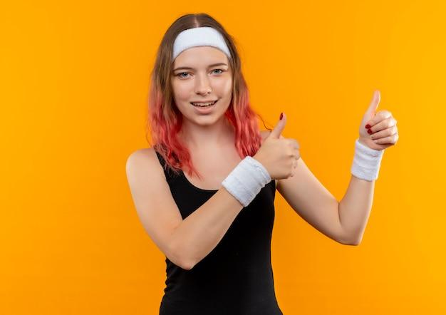 Mulher jovem fitness em roupas esportivas sorrindo alegremente mostrando os polegares para cima com as duas mãos em pé sobre a parede laranja
