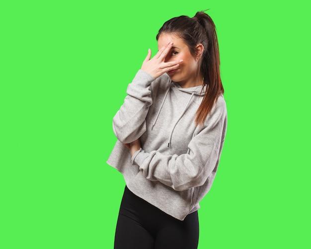 Mulher jovem fitness envergonhada e rindo ao mesmo tempo