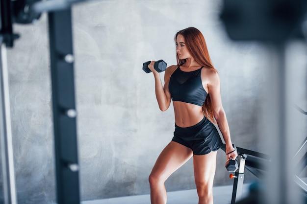 Mulher jovem fitness está no ginásio com halteres nas mãos.