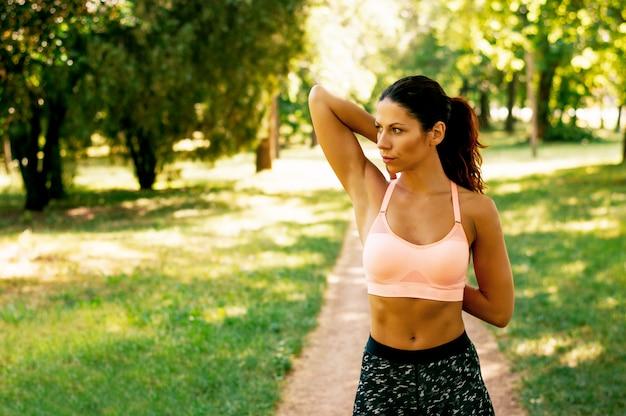 Mulher jovem fitness, esticando os braços antes de fazer exercício
