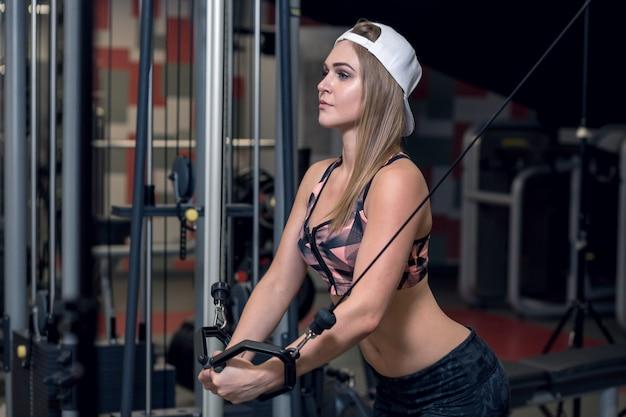 Mulher jovem fitness executar exercício com máquina de exercício cabo crossover no ginásio