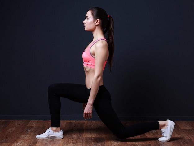 Mulher jovem fitness fazendo agachamento estocada
