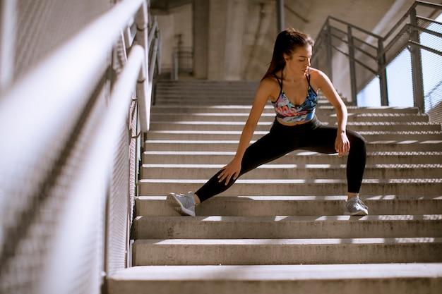 Mulher jovem fitness fazendo exercícios ao ar livre