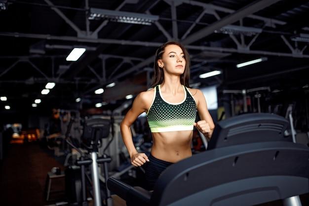 Mulher jovem fitness fazendo exercícios cardio no ginásio correndo em uma esteira.