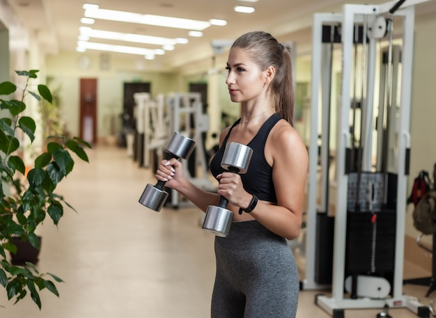Mulher jovem fitness fazendo exercícios de levantamento com halteres na mão na academia. treinamento funcional com pesos livres