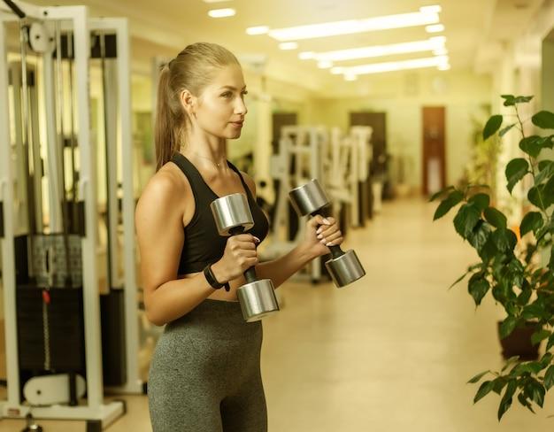 Mulher jovem fitness fazendo exercícios de levantamento com halteres na mão no ginásio. treinamento funcional com pesos livres