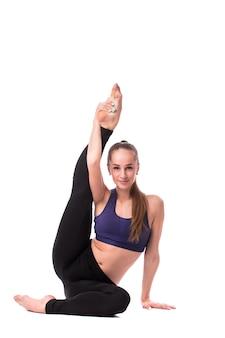 Mulher jovem fitness fazendo ioga em fundo branco