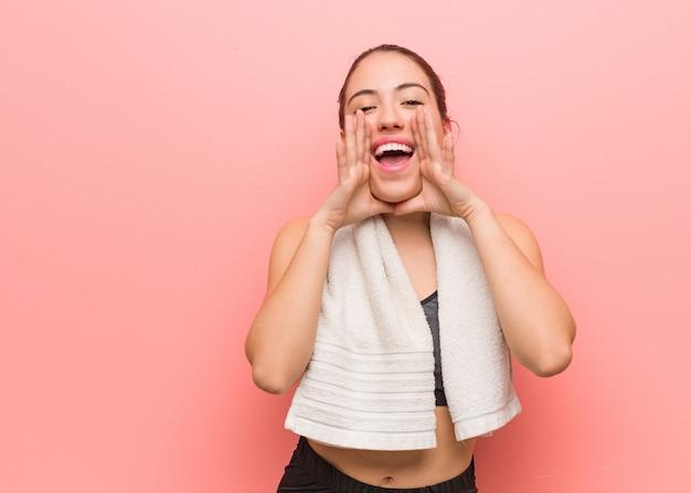 Mulher jovem fitness gritando algo feliz para a frente