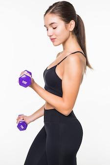 Mulher jovem fitness malhar com halteres isolado na parede branca
