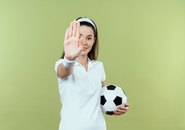Mulher jovem fitness na cabeça segurando uma bola de futebol, fazendo sinal de pare com a mão, sorrindo, olhando para a câmera em pé sobre a luz de fundo