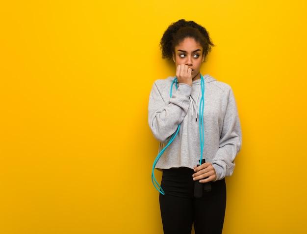 Mulher jovem fitness preto roer unhas, nervoso e muito ansioso. segurando uma corda de pular.
