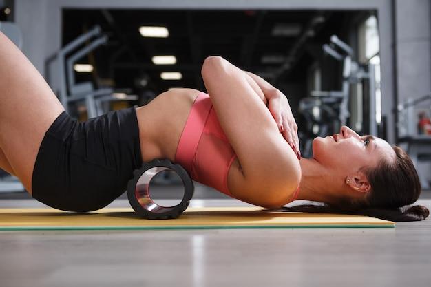 Mulher jovem fitness relaxando as costas no rolo de espuma na academia após o exercício