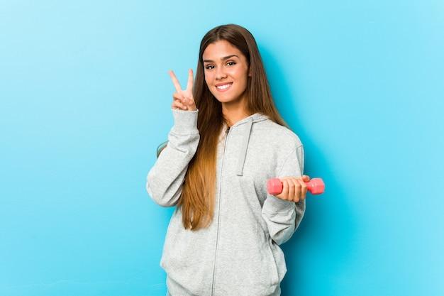 Mulher jovem fitness segurando um peso, mostrando sinal de vitória e sorrindo amplamente.