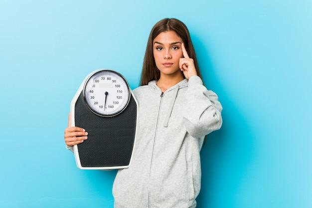 Mulher jovem fitness segurando uma balança apontando seu templo com o dedo, pensando, focado em uma tarefa