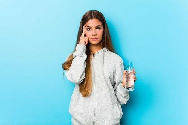 Mulher jovem fitness segurando uma garrafa de água, apontando seu templo com o dedo, pensando, focado em uma tarefa.