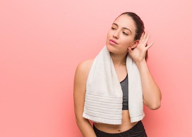Mulher jovem fitness tentar ouvir uma fofoca