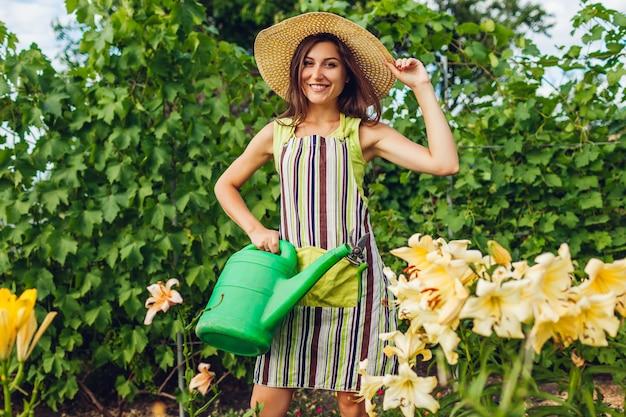Mulher jovem, flores molhando, com, lata molhando, em, jardim