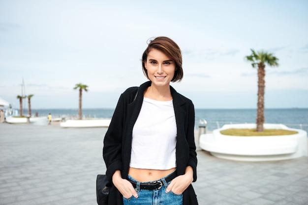 Mulher jovem fofa feliz em pé e sorrindo ao ar livre