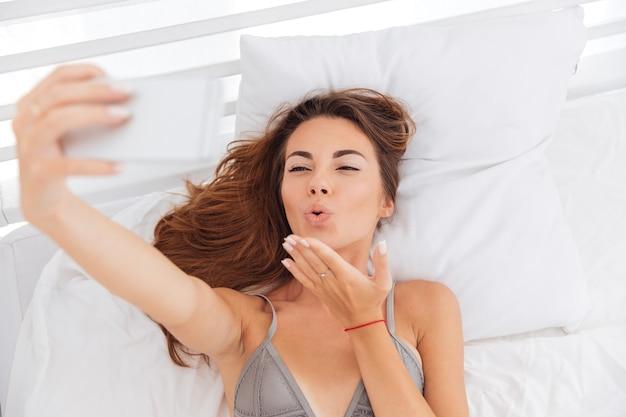 Mulher jovem fofa feliz mandando um beijo e tirando uma selfie com smatphone