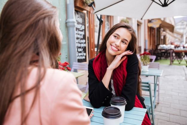 Mulher jovem fofa feliz sorrindo e conversando com a amiga em um café ao ar livre