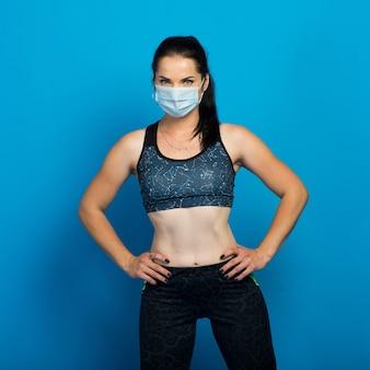 Mulher jovem forte aptidão em uma máscara facial malhando isolado no estúdio de fundo de parede azul.