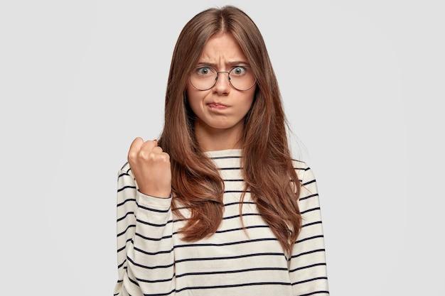 Mulher jovem forte com raiva séria mostra o punho cerrado, expressa ameaça, vestida com um suéter listrado, demonstra o poder das mulheres, olha com desprazer, posa contra uma parede branca. conceito de feminismo.