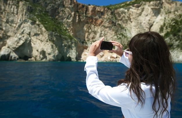 Mulher jovem fotografa a ilha na grécia
