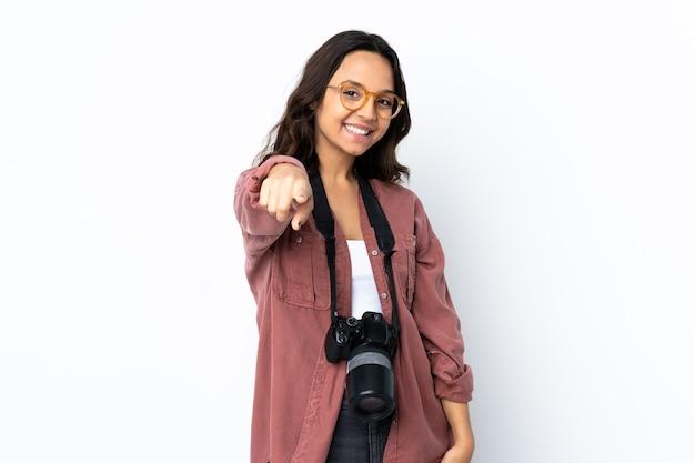 Mulher jovem fotógrafa sobre um fundo branco isolado apontando para a frente com uma expressão feliz