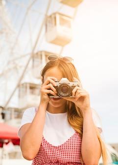 Mulher jovem, fotografar, com, câmera, em, parque divertimento
