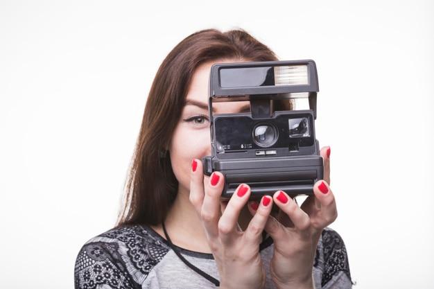 Mulher jovem, fotografar, com, câmera instantânea